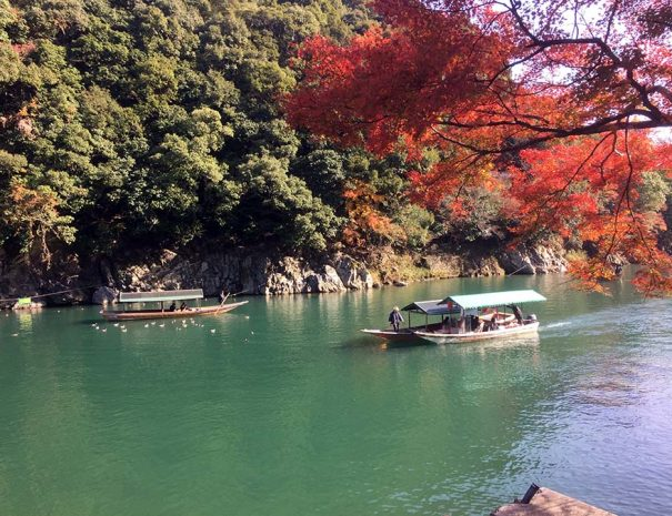 Arashiyama Kyoto traditional wooden boat on Katsura river in autumn photo